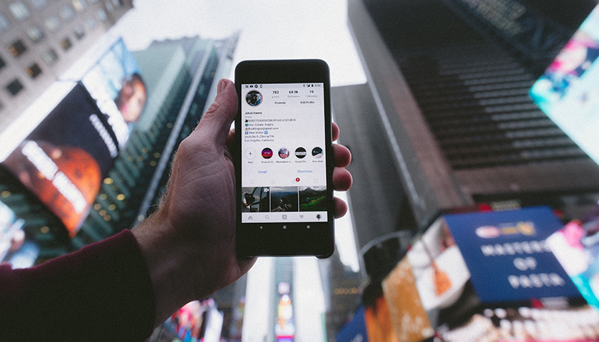 Person holding phone up in Times Square.