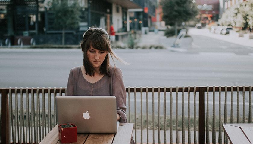 Woman on laptop working outside